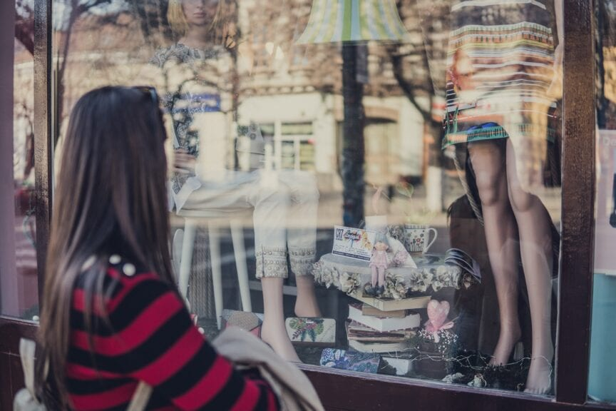 woman standing near store while looking at the mannequin