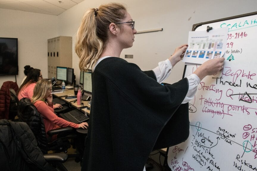 woman in black blazer writing on white paper